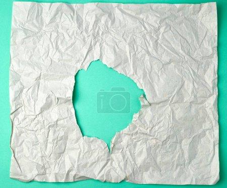 Photo pour Feuille de papier grise effilochée avec un trou, dos vert, fond abstrait - image libre de droit
