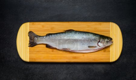 Raw Trout Fish on Wooden Chopping Board