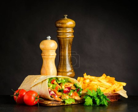 Photo for Shawarma with French Fries, Salt mill, Pepper grinder and Fresh Vegetables - Royalty Free Image