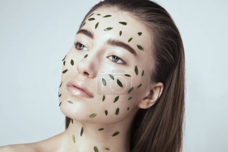 Girl with leaves mask on face
