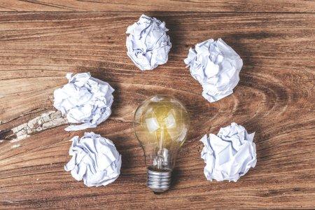 Photo pour Concept de grande idée avec papier de bureau froissé et ampoule debout sur la table - image libre de droit
