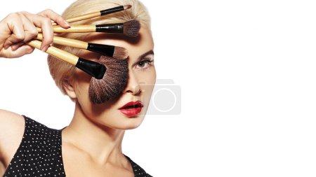 Photo pour Soins de beauté. Fille avec pinceaux de maquillage. Maquillage de mode pour femme sexy. Relooking. Maquilleuse Appliquant Visage sur fond blanc. - image libre de droit
