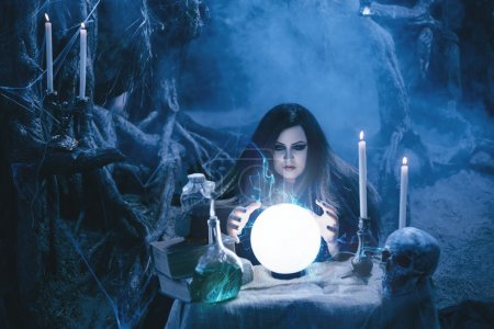 Attractive witch doing magic in the magic lair.