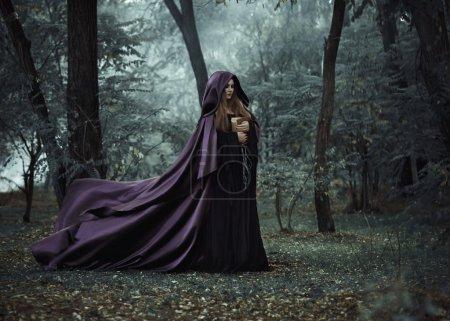 Wicked witch in a long dark cloak wandering in woods