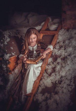 Photo pour Enfant est assis dans les escaliers lisant un livre, dans un style Cendrillon fabuleux.Beaux cheveux longs, tenue de luxe, beau sourire.Fantastique décoration Studio.Fashion toning.Creative couleur . - image libre de droit