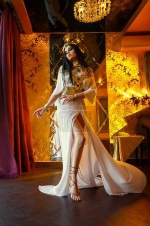 Photo pour Jeune reine dans les chambres riches. La fille est vêtue d'une robe grecque et de bijoux en or avec des serpents et des scarabées . - image libre de droit
