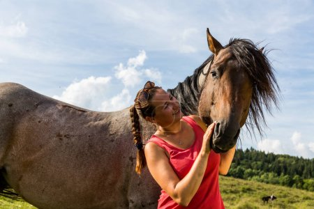 Girl with a horse on a field in Slovakian region Orava