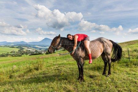 Girl sitting on a horse on a field in Slovakian region Orava