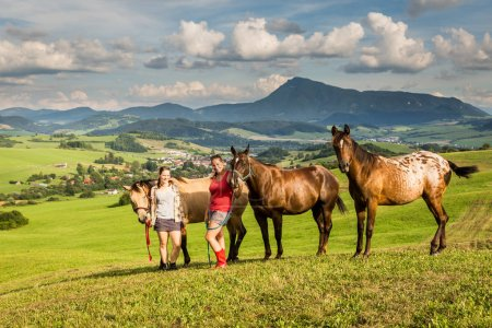 Two girls with horses on a field with mountains in Slovakia