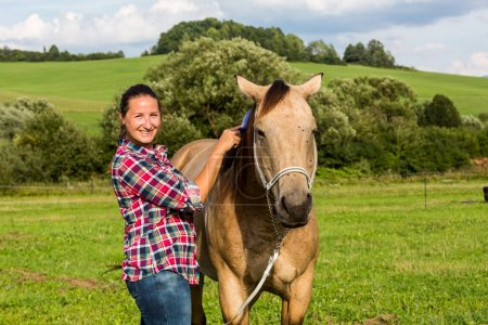 Girl brushing horse's hairs in meadow in Slovakia