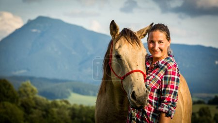 Girl with a blue and red mapped shirt with a horse in Slovakia