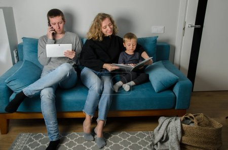 Photo for Calm young family with a small son are sitting on the couch, happy parents with a small preschooler. Office at home. Quarantined Family. Dad works on the tablet, mother with a child reads a book. - Royalty Free Image