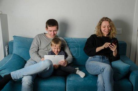 Photo pour Calme jeune famille avec un petit fils sont assis sur le canapé, parents heureux avec un petit enfant d'âge préscolaire. Bureau à la maison. Famille en quarantaine. Papa travaille sur la tablette, maman parle au téléphone, et l'enfant lit un livre . - image libre de droit