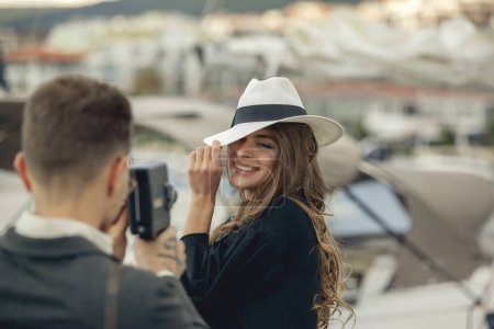 Photo for Young man taking pictures of his girlfriend on retro vintage camera. Attractive girl in hat smiling and posing for the best picture. Happy married romantic adult couple having fun, playing, fooling. - Royalty Free Image