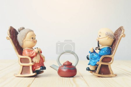 Grandma and grandpa dolls in chinese uniform style standing on wooden background. in chinese new year