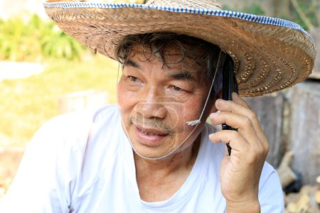 Photo for Senior Asian man with a hat made of bamboo and palm leaves shaped like an inverted basin in northern Thailand on the phone talking with his business outdoor in the garden - Royalty Free Image
