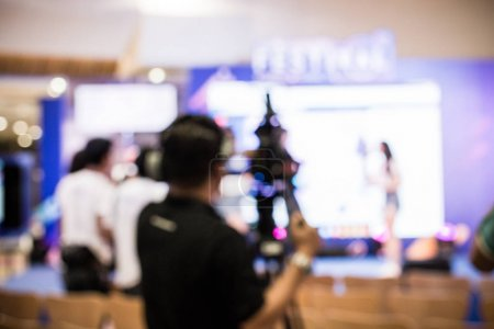 Photo pour Image floue du jeune cameraman à l'aide d'un caméscope professionnel dans la porte de l'événement, concert de musique de spectacle ou mini pour le tir des film vidéo et diffusion en direct pour la télévision en ligne commerciale de tournage - image libre de droit