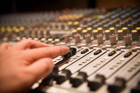 Photo pour Gros plan mains d'ingénieur du son réglage contrôleur de mixage audio pour l'équipement de studio et musique live. Il s'agit d'un système audio de qualité pour les professionnels. lumière de ton & effet vintage dans la salle de contrôle. - image libre de droit