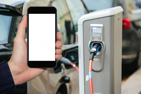 Hand with phone on a background of electric cars