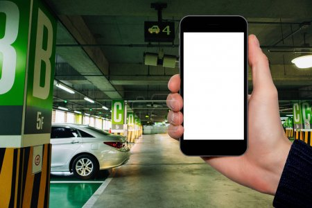 Hand with a smartphone on the background of car parking