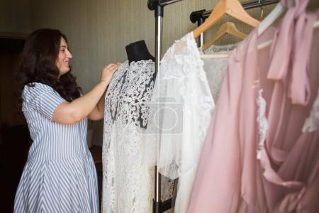Dress designer making lace wedding dresses.