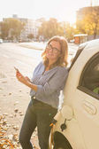 Young woman is standing near the electric car and holding smartphone