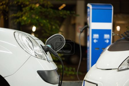 Electric car charged on a charging station in a indoor parking