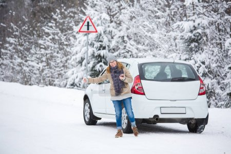 Young woman hitchhiking on the snow-covered winter road.