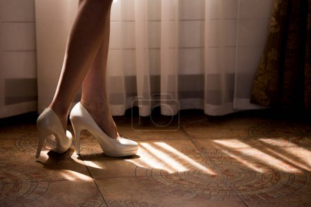 A woman with bare legs in white shoes on high heels