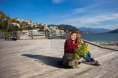 Happy girl traveler sits on a wooden pier and holds a bouquet of flowers of mimosa in hands.