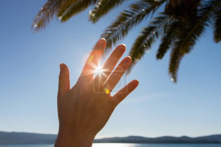 A woman shields the sun with her hand