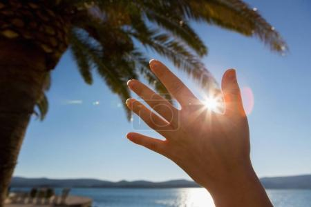 The woman shields the sun with her hand