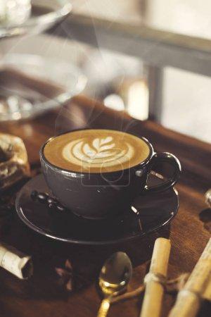 cup of coffee with latte art on vintage wooden table