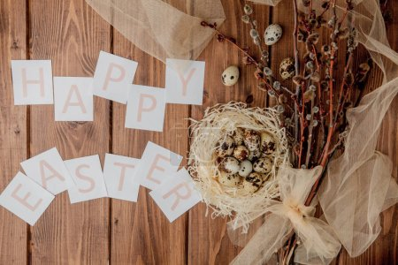Flat lay composition of quail eggs and card with text Happy Easter on wooden table. Top view.