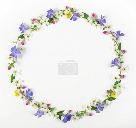 Photo for Round frame wreath made of spring wildflowers, lilac flowers, pink buds and leaves isolated on white background. Top view. Flat lay. - Royalty Free Image