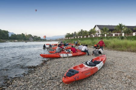 Vang Vieng, Laos - November 2015: Hot air balloons flying over Nam Song River and tourist kayaks in Vang Vieng, popular resort town in Lao PDR