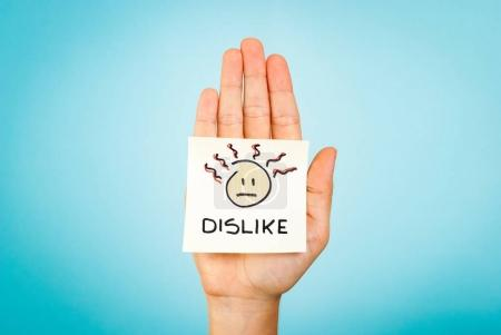 Dislike emoticon note on hand with blue background