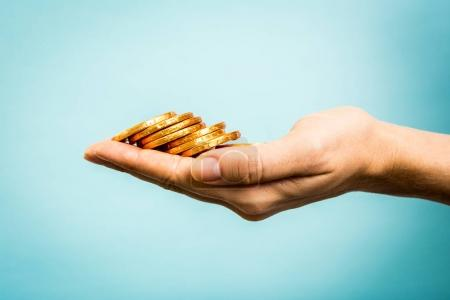 Hand holding golden coins concept on blue background. Business concept