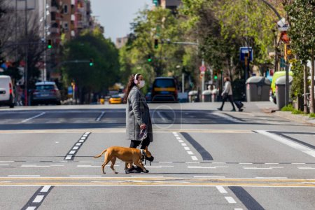 Photo for Barcelona, Spain. 8th April, 2020. Woman walking a dog over an almost empty Arago street in central Barcelona during the Covid state of alert - Royalty Free Image