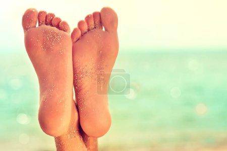 Photo pour Parfait nettoyer pieds femelles avec sable de mer sur la plage. . Spa, gommage et soins des pieds. - image libre de droit