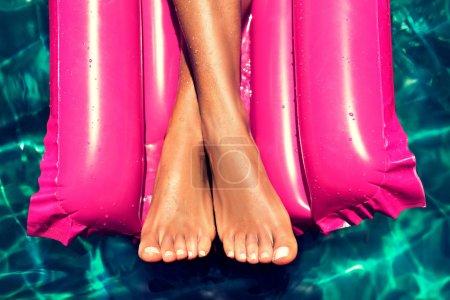 Pies bien arreglados bronceados en la piscina