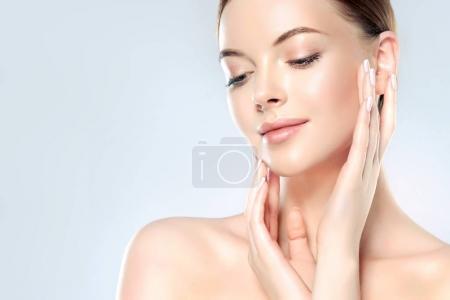 Photo pour Belle jeune femme avec peau fraîche propre toucher son propre visage. Traitement du visage. Cosmétologie, beauté et spa  . - image libre de droit