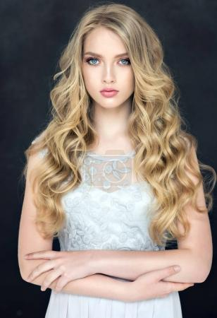 Photo for Blonde fashion  girl with long  and   shiny curly hair .  Beautiful  model  in light blue dress with wavy hairstyle . - Royalty Free Image