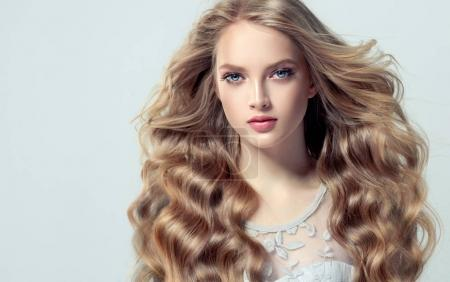 Photo for Beautiful blonde young woman with long  and shiny curly hair. Attractive model with wavy hairstyle - Royalty Free Image