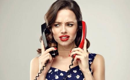 annoyed girl with old  telephones