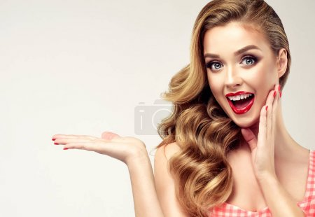 Photo for Woman surprise showing product .Beautiful girl  pointing to the side . Presenting your product. Expressive facial expressions emotions - Royalty Free Image