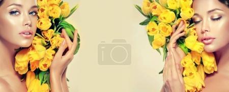 brunette woman holding yellow tulips