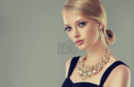 Photo pour Belle fille avec des bijoux ensemble. Femme dans un collier avec une bague, boucles d'oreilles et un bracelet. Beauté et accessoires. - image libre de droit