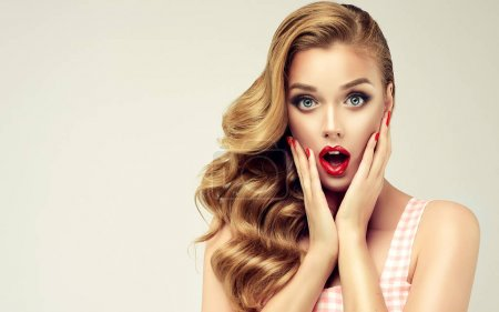 Photo for Woman with red lips and nails surprise holds cheeks by hand .Beautiful girl  with curly hair surprised and shocked looks on you . Presenting your product. Expressive facial expressions - Royalty Free Image
