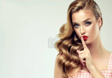 Beautiful  model girl with long ,curly hair .  Red lips and nails manicure .Woman holds a finger on her mouth a secret